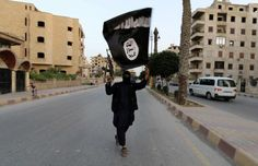 A member loyal to the ISIS waves an ISIS flag in Syria. The group, also known as the Islamic State, has purportedly created a presence for itself in London. -- ISIS supporters seen handing out Islamic propaganda across London that encourages people to move to Middle East  http://nydn.us/1l3H9SF