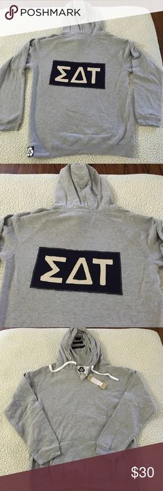 NWT Sigma Delta Tau gray pull over sorority hoodie NWT Sigma Delta Tau gray pull over hoodie w/ navy & white logo. Size AL. 60% poly 40% cotton.  V neck, draw string in hood, sorority lettering logo appliqué on back & solid front. Front kangaroo pockets. Made in USA. $62 retail. Rare and one of a kind. #greek #life #college #university #sigma #delta #tau #sorority #pledge #gray #navy #pullover #big #little #sister #nwt #hoodie #vneck Never used. Smoke free home. Check closet for similar…