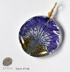 Hand pressed, dried Irises sealed with high quality resin. Nature is so exquisite that it deserves to be preserved! This pendant is absolutely beautiful and will complement any outfit! Bail is hand wired for a more natural look. Pendant measures approximately 1.0 and is extremely lightweight. Chain is not included.  The pendant arrives in organza bag which makes gift giving easy! FREE shipping makes this a very affordable gift! All my resin creations are hand made by me in my home workshop…