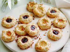 Jam Thumbprint Cookies : Keep the holidays simple yet festive with Ina Garten's buttery thumbprint cookies rolled in sweet shredded coconut. A drop of raspberry or apricot jam adds rich, jewel-toned color.