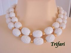 This lovely classic designer signed Trifari necklace features two strands of textured white plastic beads combined with ornate goldtone spacer beads.    The necklace is sig... #vintage #jewelry #fashion #antique