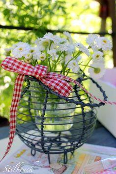 El vas amb flors dins de una ouera de filferro antiga