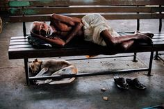 Steve McCurry, Bombay/Mumbai, India, 1996, INDIA-10205. A railway porter sleeps on the bench waiting for the train to arrive in the station. Porters form an entire economy system on their own in Delhi, and operate on licenses that are valid for the lifetime of the bearer. Bombay (Mumbai), India, 1996.