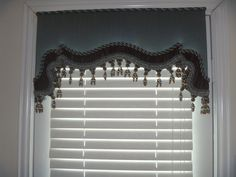 cornice board for a bedroom door  with chocloate silk shirred banding , brown and blue rope trim in  2 sizes and beaded brown and blue tassel trim
