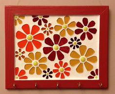 Porta-chaves com borda vermelha e flores em mosaico de vidro, em tons de vermelho, laranja e âmbar. Mosaico feito sobre base de madeira, com 5 ganchos para pendurar. Área do mosaico: 20 x 15cm.