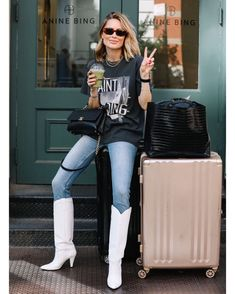 Grey graphic t-shirt+skinny jeans+white cowboy-look midi boots+black chain shoulder bag+black travel-bag+sunglasses+necklaces+pink suitcase. Soft Grunge, Look Jean, Nyc, Anine Bing, Jeans Slim, Skinny Jeans, Star Fashion, Fashion Brand, Travel Bag