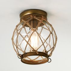 """Jute Rope Lattice  Aged brass finish hardware, clear glass globe and nautical rope laced into a net bring to mind days of crabbing and fishing. 60 watts medium socket. (9""""Hx8""""W)"""