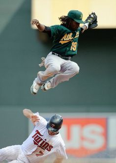 Jemile Weeks #19 of the Oakland Athletics leaps over the sliding Joe Mauer #7 of the Minnesota Twins on May 28, 2012 at Target Field in Minneapolis, Minnesota. The Twins defeated the Athletics 5-4