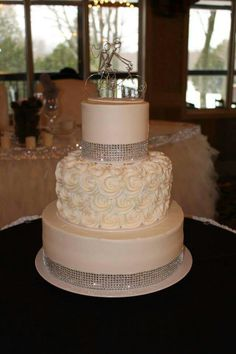 3-tier wedding cake with rosettes and bling. Also featuring a unique cake…