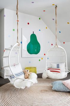 Colorful contemporary girls' bedroom features two Serena & Lily White Hanging Rattan Chair hung from a sloped ceiling over a round jute rug and topped with sheepskin pelts and blue and red striped pillows.