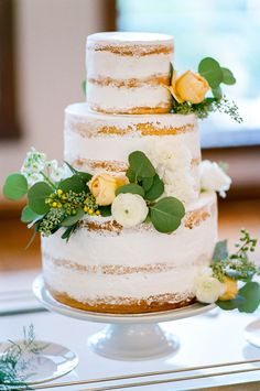 White and Yellow Wedding Cake with Fresh Flowers and Greenery