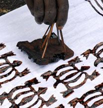 A textile  artist hand-stamps a cloth with the Adinkra symbol Denkyem, the African crocodile, which symbolizes adaptability.