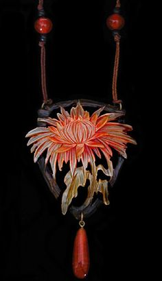 ART NOUVEAU Chrysanthemum Pendant. An engraved horn chrysanthemum pendant with original beads and silk chord. French c. 1900. Unmarked. Size: Length of pendant 9.8 cm. Width 6.1 cm. Approximate length of chord 82 cm.