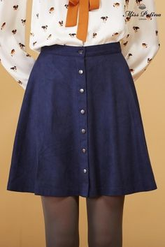 A navy skirt, with a center front row of buttons. Too bad we don't get a better look at the blouse with its big ribbon. (Miss Patina)