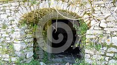 Stone archway, entrance to agricultural storeroom,  taken at the deserted town of Old Perithia, in the foothills of Mount Pantokrator, Corfu, Greece. Old Perithia once had 1200 residents and had eight churches. Some buildings date from 13th Century. The town was abandoned after  earthquake damage.