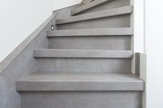 Een prachtige witte trap afgewerkt met rvs en next step treden in de