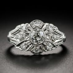 An original and highly distinctive Art Deco dazzler, hand-fabricated in platinum, circa 1925. This exceptional and absolutely breathtaking Jazz Age jewel features a central bezel-set European-cut diamond, weighing .60 carat, embellished all around with delicate hand piercing; millegrain and decorative engraving; and 10 small glittering round diamonds. As a finishing flourish, the top of the ring shank is masterfully hand-engraved with a classic acanthus leaf motif. Superlative and stunning!
