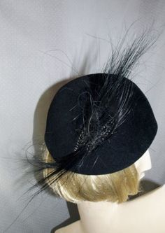 Egret Feather Hat   by Jack McConnell For Walton-Pierce     Art Deco Hat Rare Egret Feathers Jack McConnell Felt Black Helmet Beaded -- (1930-1946) Sprays of delicate, curled egret feathers; Curled rare egret feather sprays are attached with an holder covered with black faceted glass navettes and chatons and hand sewn on the underside; Workmanship is so expert that the stitches on the underside are hardly visible; Egret feathers are arranged on the hat's right side to form a span of 12…