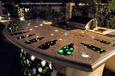 outdoor concrete bar top with wine bottles and lightsembedded...