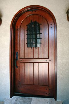 """Augustine Fortress"""" by Fine Woodworks Custom Doors. This round top, solid mahogany door features a door-in-door security window. Made of Hand-Carved Honduran Mahogany. Visit our website for additional photos and pricing. Woodworking Logo, Woodworking Joints, Woodworking Books, Fine Woodworking, Woodworking Ideas, Rustic Doors, Wooden Doors, Security Door, Custom Wood"""
