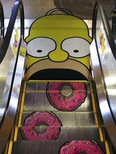 "this form of art is ""Street art"" I find it awesome because its homer simpson painted at the end of an escalator and hes opening his mouth and as the stairs move own theres donuts going into his mouth.. GENIUS"