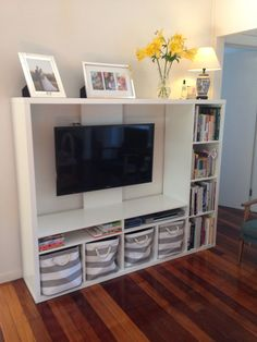 IKEA Lapland tv unit with books and storage baskets.