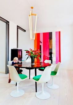 Bright dining space with colorful art, a large chandelier, and mod chairs