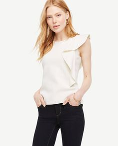 """In a clever play of proportions, a single cascading ruffle lends a touch of modern asymmetry to this flattering shell. Jewel neck. Sleeveless. Side slits. 22 3/4"""" long."""