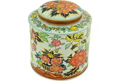 """Round English tea tin with an embossed Asian floral motif. Marked """"Designed by Daher; Long Island, NY; Made in England."""""""