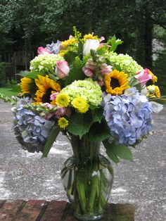 Sunflowers and hydrangeas with pink rose and snapdragon accents