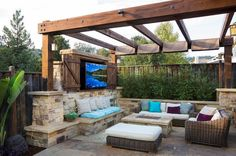 Pergola with outdoor TV, fireplace and cozy seating [Design: West Bay Landscape]