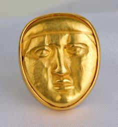 """""""Repossé Gold Mask Ring"""", ca. 4th-3rd Century BC. An ancient Greek gold miniature male mask mounted in a modern 18+ Kt gold ring setting. The repossé mask bears several tiny holes on at its edges (only visible from the back) indicating that it was originally used as an appliqué attachment to a larger piece of jewelry or clothing."""