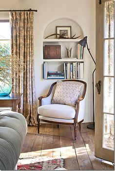 love: old wood floors, built in arched bookshelves, french door, curtains, everything =)