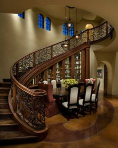 An elegant wood staircase with an ornate wrought iron railing curves up and around this Mediterranean-style dining room. A tiered chandelier hangs in the center of the room, drawing the eye up to the impressive two-story ceilings.