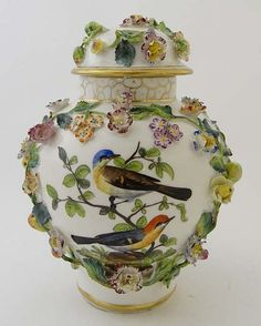 A late 18thC / early 19thC Meissen ? porcelain jar and domed cover finely painted with exotic birds in branches within a profusion of various applied flowers and leaves, below gilt marbled neck. The domed cover with further encrusted flowers. Indistinct blue mark to base.