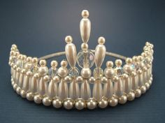 measures 2 inches at its highest point and is very elegant.     This tiara has been created using white half inch faux drop pearls, 4mm, 6mm white glass pearls, 6mm machine cut crystals AB and one 12mm crystal AB attached to a 3mm silver tiara band.     This tiara can be worn with or without a veil     Small elastics have been attached to help with the placement