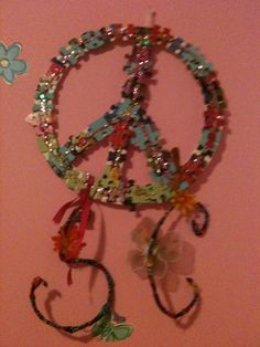 Peace sign with initials made out of puzzle pieces, fabric, and wire