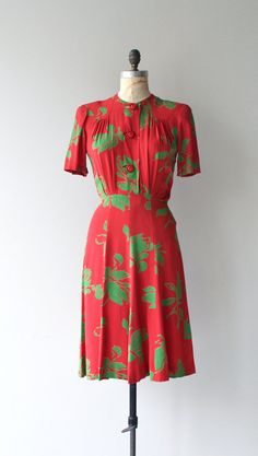 Vintage 1940s red rayon dress with green fronds, short sleeves, large buttons down the bodice, gathered shoulders, fitted waist and button side waist.