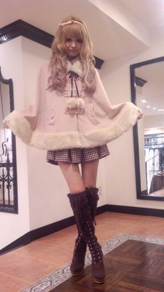 Cute, sweet gyaru: Light pink poncho with white faux fur details. Multicolored, pleated skirt. Brown thigh-high boots with faux fur details.