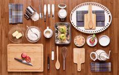 Blick von oben auf einen Tisch mit Backzubehör und den Zutaten für einen Apple Crumble: u. a. APTITLIG Hackblock aus Bambus, SMARTA Kuchen-/Pieform in Weiß, GUNLIS Geschirrtuch Karos, IDEALISK Mehlsieb aus Edelstahl und SKALAD Schälmesser in Grau