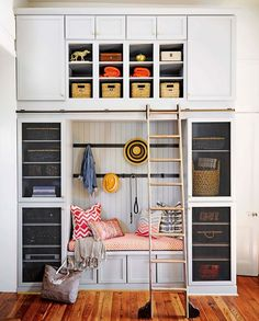 A floor-to-ceiling bank of cabinets by the side door functions as a mudroom, with cubbies for bookbags and soccer balls. The built-in bench cushion is covered in Portico from Thibaut's Portico collection of Sunbrella fabrics. The ladder is by CSH. Chic Beach House, Tall Shelves, Mug Design, Inspiration Design, Design Ideas, Built In Bench, Built Ins, Mudroom, Decoration