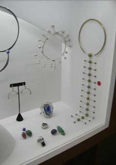 Store window displaying mid century modern jewelry. | I can pieces from Art Smith, Betty Cook and Elsa Freund. Does anyone know the artist of the lovely long piece with the red sticker next to it?
