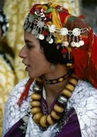 A Berber woman from Ouarzazate in the High Atlas Mountains wears a necklace of old imitation amber and silver balls interspersed with red fe...