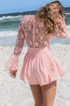 4acd0e8862d5 Feel pretty this summer in this flirty blush colored romper! Features sheer  lace flare sleeves and pleated shorts on the bottom. Material is polyester  Model ...