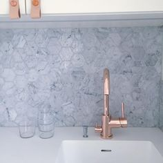 Our Rose Gold kitchen mixer EVO184 in front of the hexagonal marble tiles makes a great combo. The copper knobs with Rose-colored handles enhances the classic white cabinet. Stylish! #kök #köksinspiration #köksblandare #EVO184 #rosegold #rose #kitchen #kitchenfaucet #kitcheninspo #kitchendesign #tapwell