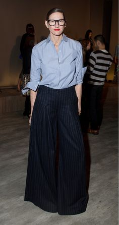 A striped button-up shirt is worn tucked into striped wide leg trousers, glasses, and a bold red lip.