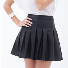 """Faux leather pleated skirt Love 21 - The edge of sleek faux leather with the upscale details of classic East Coast prep - your traditional schoolgirl skirt this definitely is not. Large-scale box pleats and a full, flared skirt.  Concealed side zipper Woven, unlined Shell: 100% polyurethane; Backing: 85% rayon, 15% polyester 16.5"""" full length, 29"""" waist Measured from Small Machine wash cold ❌ no trades! ❌ no lowball offers, you will be blocked! ✔️ yes to fast shipping! ✔️ yes to discounted…"""