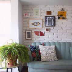 um sofá, quadrinhos e uma samambaia alegrando a mesa lateral! precisa de mais??? porque a gente acredita em casas com menos ostentação e mais emoção...
