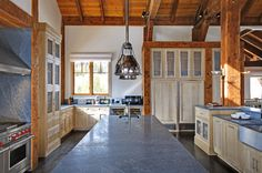 Farmhouse Kitchen Design, interesting blue/grey stone on light cabinets with beams, industrial lights, wolf, cabinet front subzero