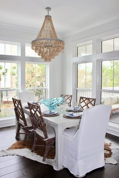 30a interior design, dining room, white slipcovered dining chairs, cowhide rug, blue white brown dining room, made goods chandelier, gabby dining chairs, lovelace interiors, lake vista, seagrove east Dining Chair Slipcovers, Brown Dining Room, Room, Interior, Coastal Dining Room, Home Decor, Dining Chairs, Interior Design, Dining Room